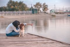 Woman playing with her dog Basset Hound by the river. Portrait of beautiful young woman playing with dog by the river. Happy woman sitting on the wooden pier royalty free stock photos