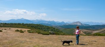 Woman playing with her dog on top of Palentina mountain. Spain. Panoramic. Woman playing with her dog on top of Palentina mountain. Spain stock images