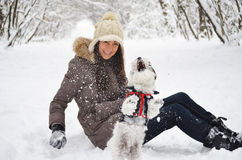 Woman playing with her dog in the winter forest Royalty Free Stock Photo