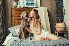 Woman playing with her dog. Young and pretty woman playing with her dog in bedroom royalty free stock photo