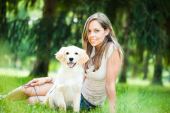 Woman playing with her her golden retriever outdoors Royalty Free Stock Photography