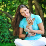 Woman playing with her little puppy in a green park Royalty Free Stock Photos