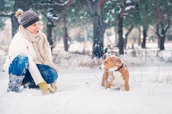 Woman playing with her pet in snow Stock Photos
