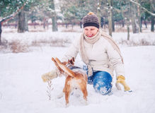 Woman playing with her pet in winter park Royalty Free Stock Photos
