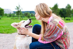 Woman playing with her puppy outdoor. Woman playing with her golden retriever puppy Royalty Free Stock Photo