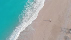 Woman playing with her  Tibetan terrier dog on the beach. In the morning on a summer day, aerial drone view stock video