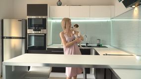 Woman playing with his dog at home stock video