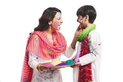 Woman playing holi with her son Stock Images