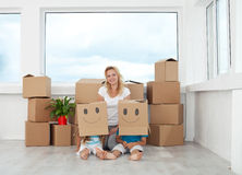 Woman with playing kids in their new home Stock Photos