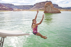 Woman Playing at the Lake. A beautiful woman goes down a water slide on a houseboat on the lake. Lake Powell, Utah or Glen Canyon National Recreation Area Royalty Free Stock Images