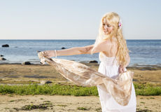 Woman playing with light scarf at beach Royalty Free Stock Image