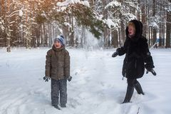 Woman playing with a little boy in a snowy winter Park. Royalty Free Stock Photos