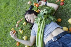 Woman playing with a mandarin. Woman on the grass with a mandarin Stock Photo
