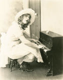Woman playing a miniature piano Stock Image