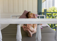 Woman playing mobile in daybed at balcony Royalty Free Stock Images
