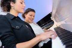 Woman playing music using piano Stock Photography