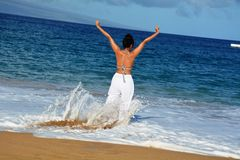 Woman playing with ocean waves Stock Photo