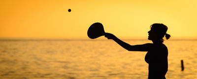 Woman playing paddle ball on the beach Stock Photo