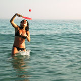 Woman playing paddle ball in the ocean Royalty Free Stock Photos