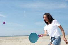 Woman playing paddle ball. Portrait of a young woman playing paddle ball at the beach Stock Image