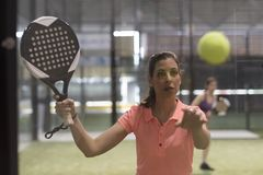 Woman playing paddle tennis, ball bounce on glass. Ready for hit royalty free stock images
