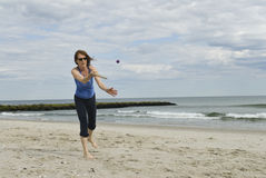 Woman playing paddleball on beach (series 3 of 3) Royalty Free Stock Photography