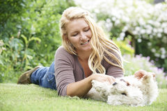 Woman Playing With Pet Dog In Garden Stock Photos