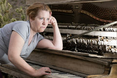 Woman Playing on Piano Looking into Distance Royalty Free Stock Images