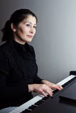 Woman playing piano Stock Image