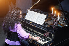 Woman playing the piano Stock Photos
