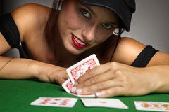 Woman playing poker at a table Stock Images