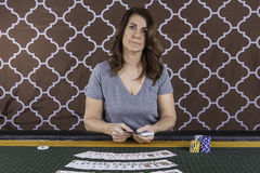 A woman playing poker at a table Stock Image