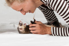 Woman playing with polecat Stock Photo