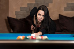 Woman Playing Pool About to Hit Ball Stock Photography