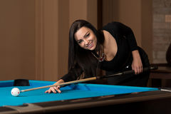 Woman Playing Pool About to Hit Ball Stock Photo