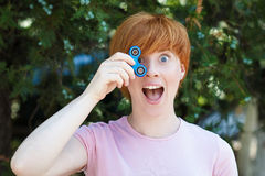 Woman playing with a popular fidget spinner toy, anxiety relief toy, anti stress and relaxation fidgets. Smilling girl in pink t-shirt is playing blue metal Royalty Free Stock Image