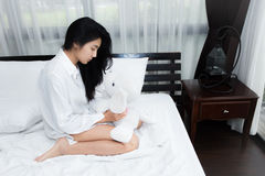 Woman playing puppy doll on the bed Royalty Free Stock Images