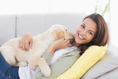Woman playing with puppy on sofa Royalty Free Stock Image