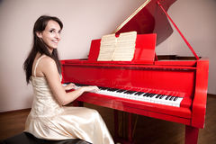 Woman playing the red grand piano Royalty Free Stock Photo