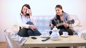 Woman playing a sad song to her friend stock footage