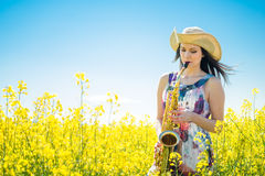 Woman playing saxophone in rapeseed field Stock Photography