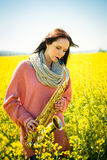 Woman playing saxophone in rapeseed field Stock Image