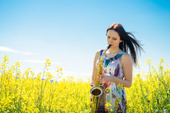 Woman playing saxophone in rapeseed field Royalty Free Stock Image