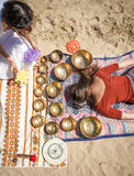Woman playing a singing bowls also known as Tibetan Singing Bowls, Himalayan bowls. Making sound massage. Stock Photos