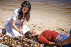 Woman playing a singing bowls also known as Tibetan Singing Bowls, Himalayan bowls. Making sound massage. Royalty Free Stock Image