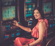 Woman playing slot machine Stock Photo