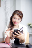 Playing smartphone. Asian woman worker smile while using smartphone Stock Images