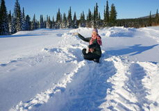 Woman playing with snow up in a sunny afternoon. Woman throws snow up in the winter forest of sunny day Stock Images