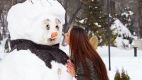 Woman playing with snowman stock video