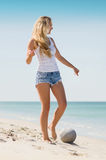 Woman playing soccer at the beach. Attractive young woman kicking football at the beach Stock Image